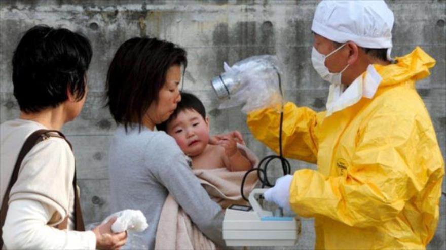 Personal médico comprueba los niveles de radiación de una mujer y su hijo en Kawamata en la región de Fukushima (Japón).