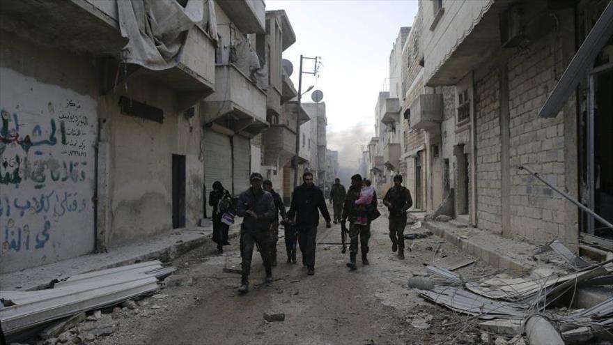 Soldados sirios caminan por un barrio recuperado en el este de Alepo.