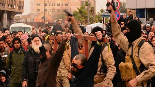 Combatientes del Estado Islámico junto a dos de sus prisioneros