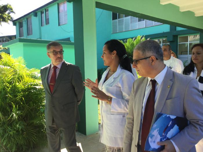 El embajador de Rusia en Cuba (izq) y el representante de la OPS recorren áreas del policlínico Camilo Cienfuegos.